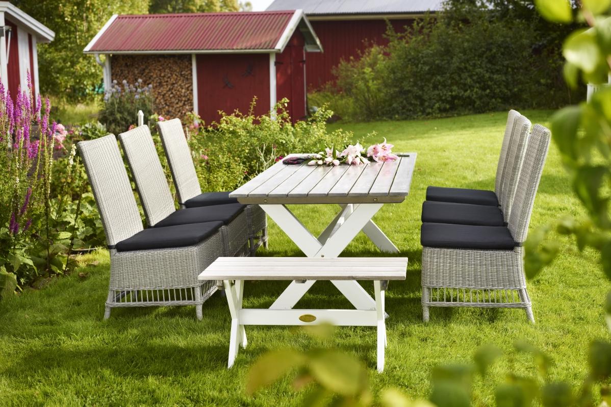 Matgrupp Glostorp med lantligt utebord i trä med kryssben och 6 stolar i konstrotting Vita